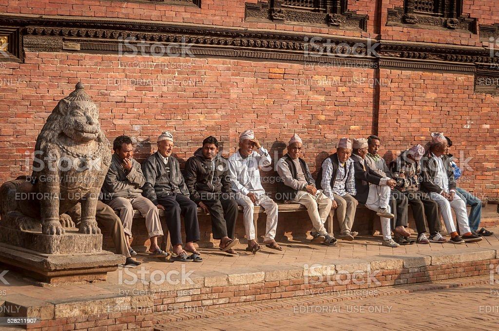 Nepalese Men Sitting on Bench, Patan Durbar Square, Kathmandu, Nepal stock photo