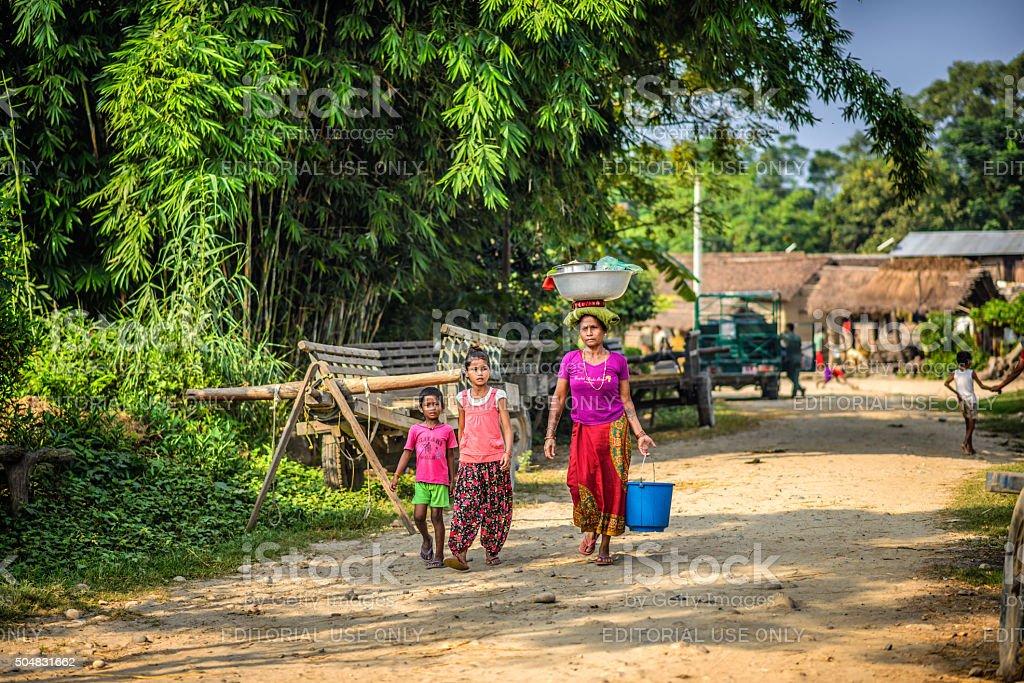 Nepalese mother with two children walk through their village stock photo