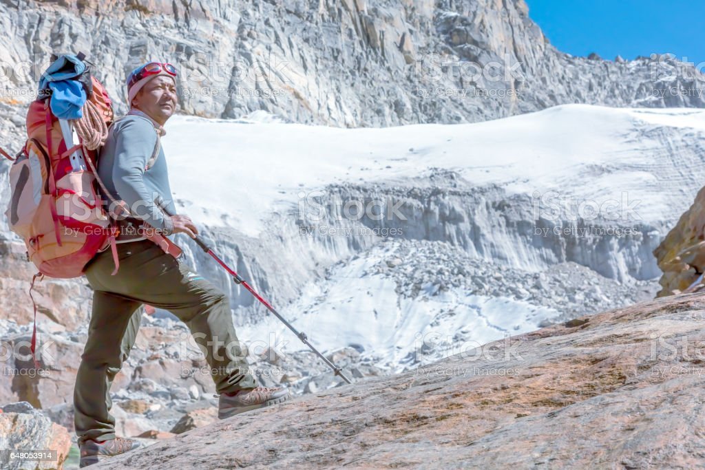 Nepalese Mountain Guide staying on top of high Rock stock photo