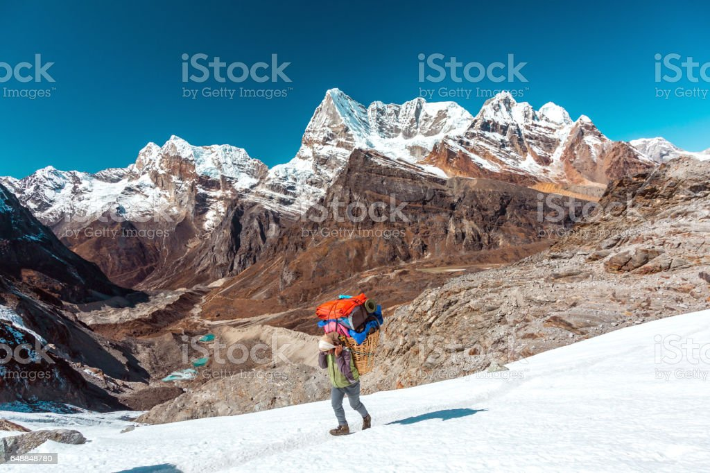 Nepalese Porter carrying Basket with luggage of mountain expedition stock photo