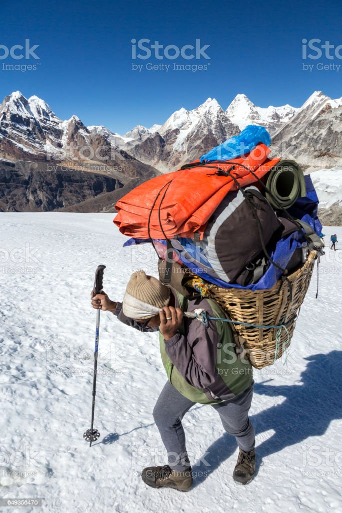 Nepalese Porter carrying Basket with Mountain Expedition Luggage stock photo