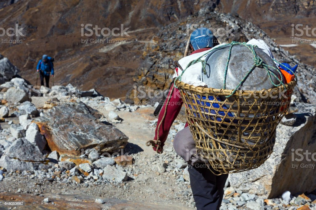 Nepalese Porter carrying Basket with rural household goods stock photo