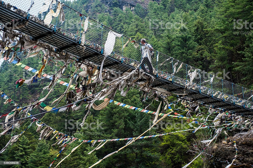 Nepalese rope swing bridge with prayer flags in the Himalayas stock photo