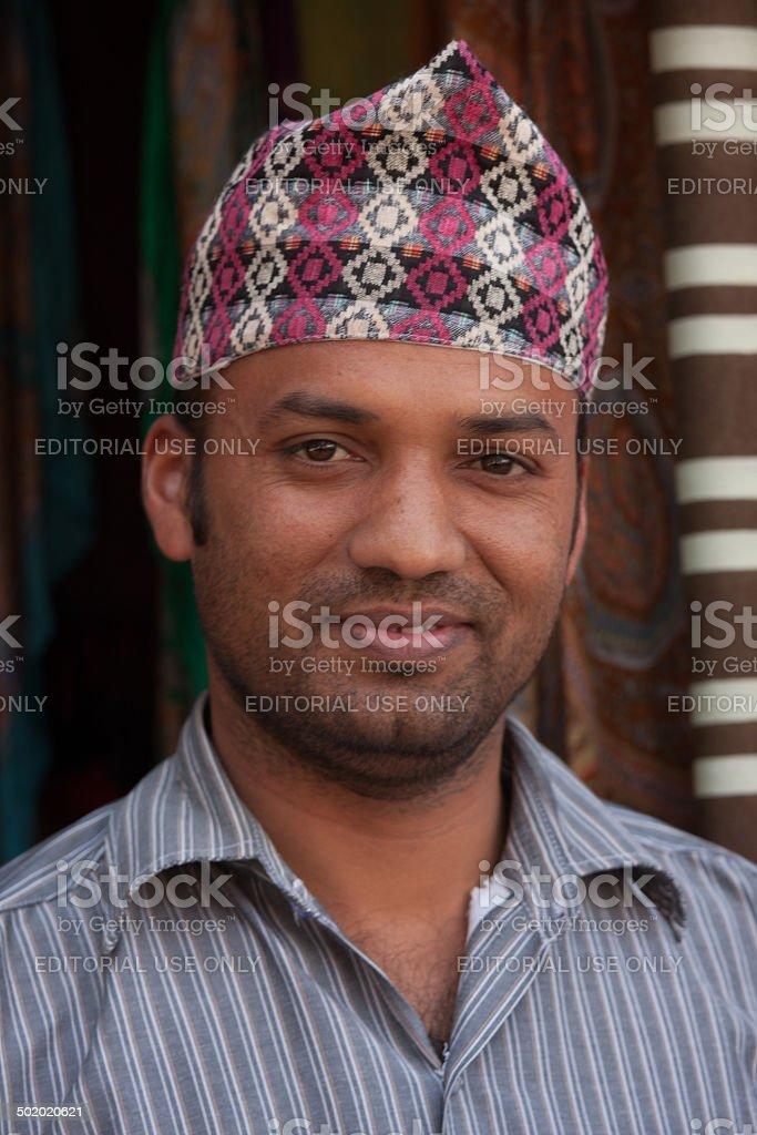 Nepalese shawl merchant wearing traditional hat stock photo