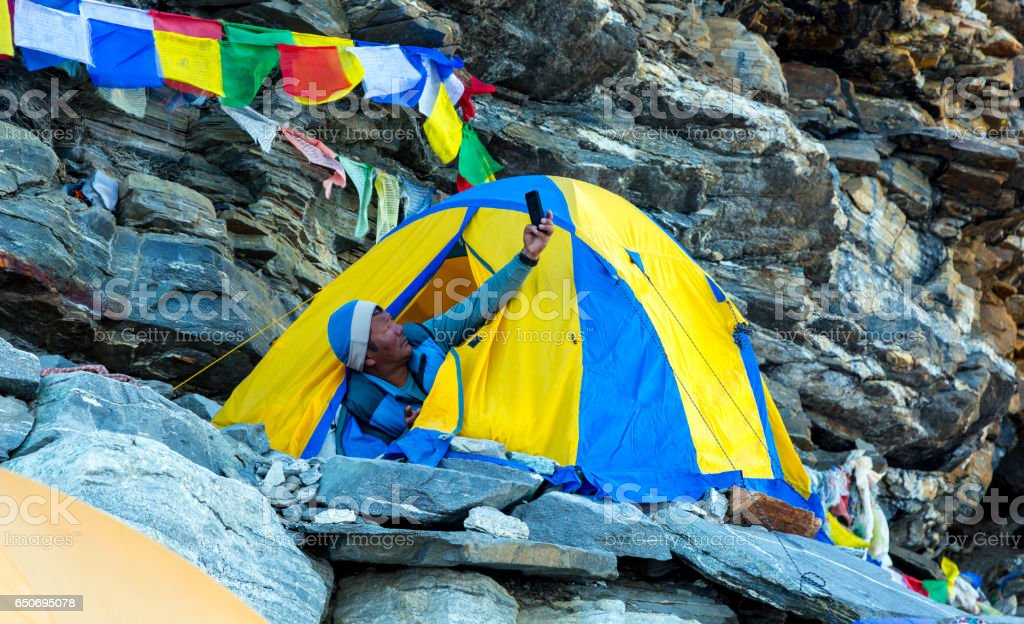 Nepalese Sherpa Mountain Climber taking Self Portrait in Tent stock photo