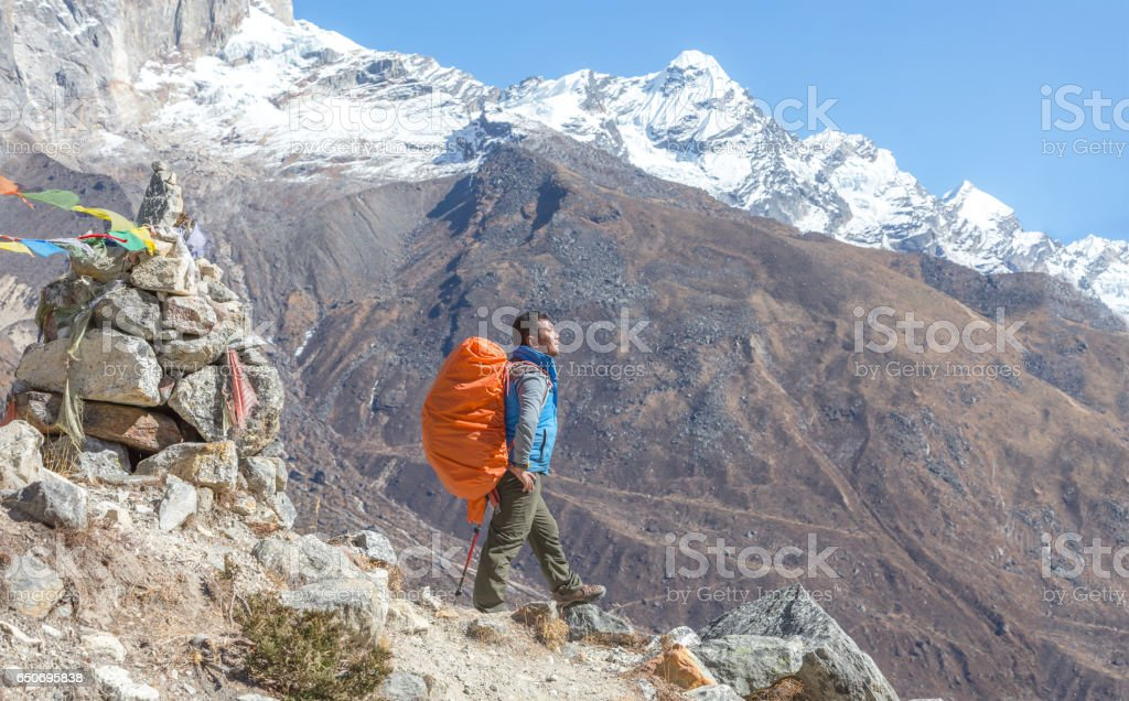 Nepalese Sherpa Mountain Guide staying on Footpath and buddhist flags stock photo