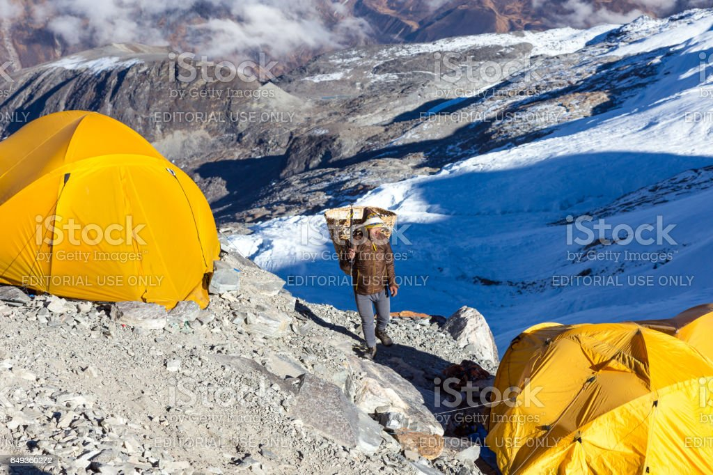 Nepalese Sherpa Porter carrying wicker Basket in Mountain Expedition Camp stock photo