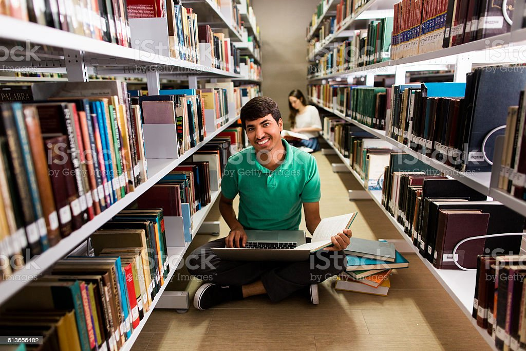 Nepalese student sitting on the floor with computer and smiling stock photo