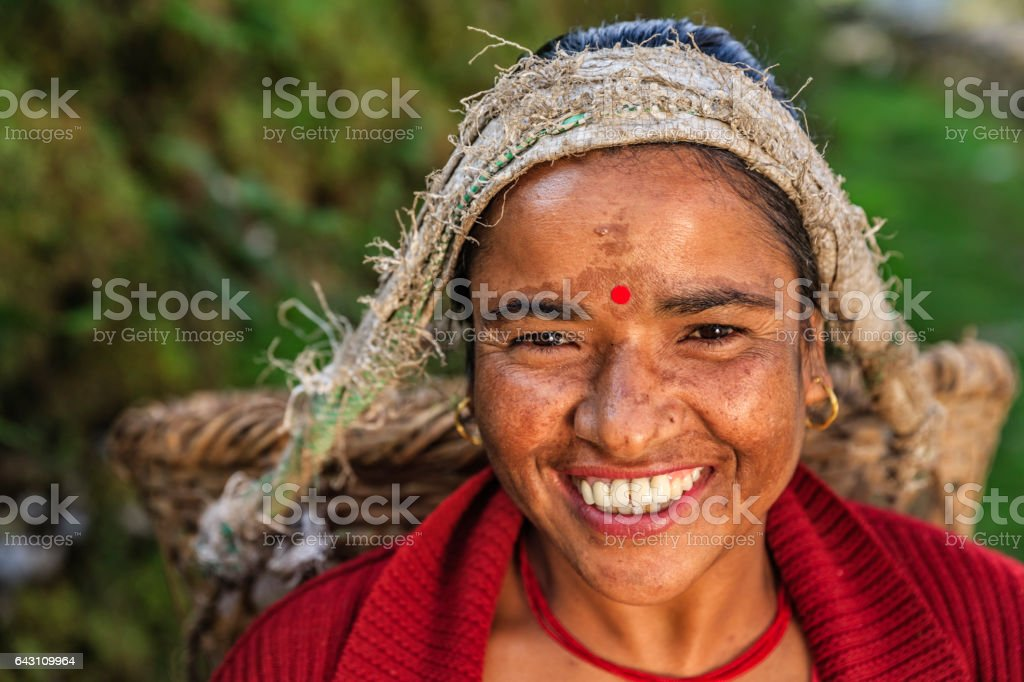 Nepalese woman carrying a basket near Annapurna Range stock photo