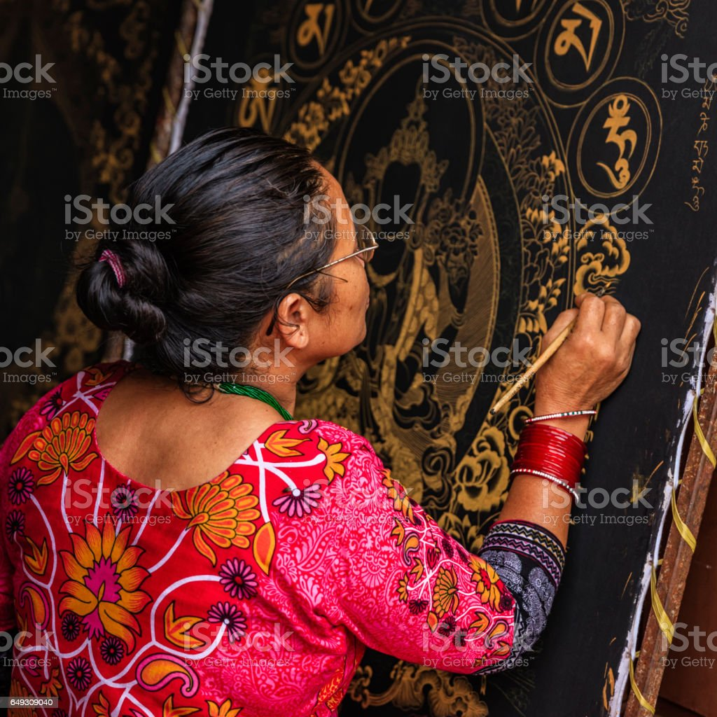 Nepalese woman painting a thanka in Bhaktapur stock photo
