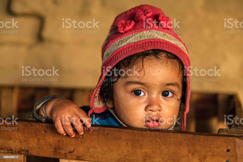 Nepali baby boy  in playpen, village near Annapurna Range stock photo