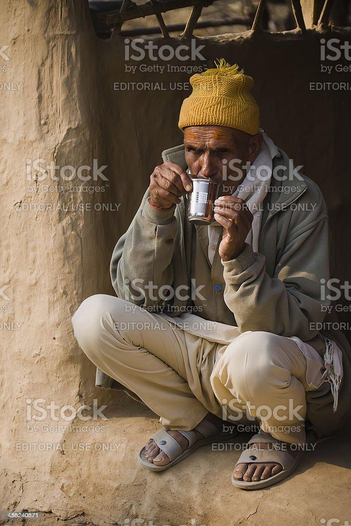 Nepali man drinking a hot tea in tharu village stock photo