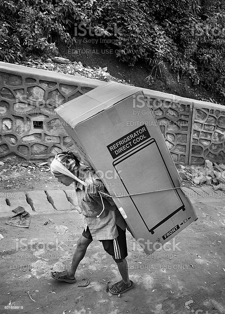Nepali porter carrying refrigerator stock photo