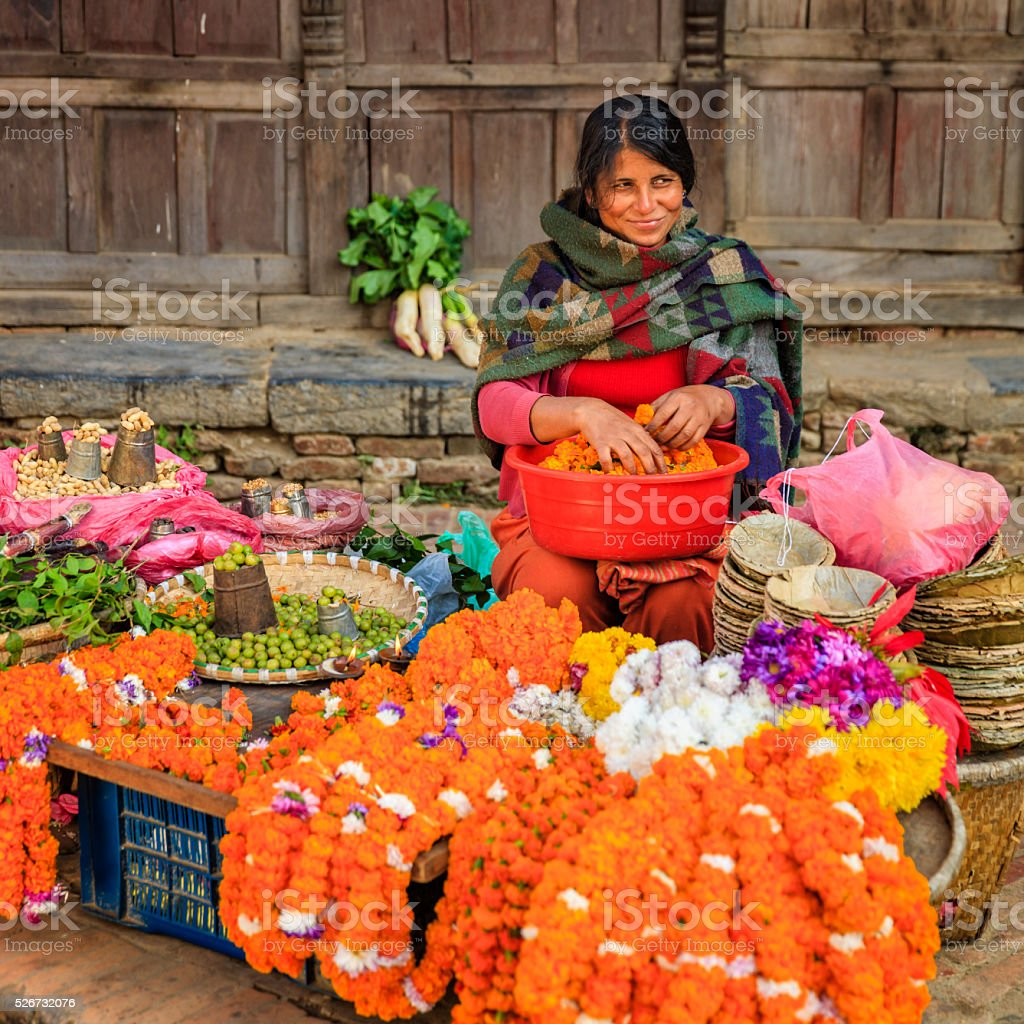 Nepali street seller selling flowers and vegetables in Patan, Nepal stock photo