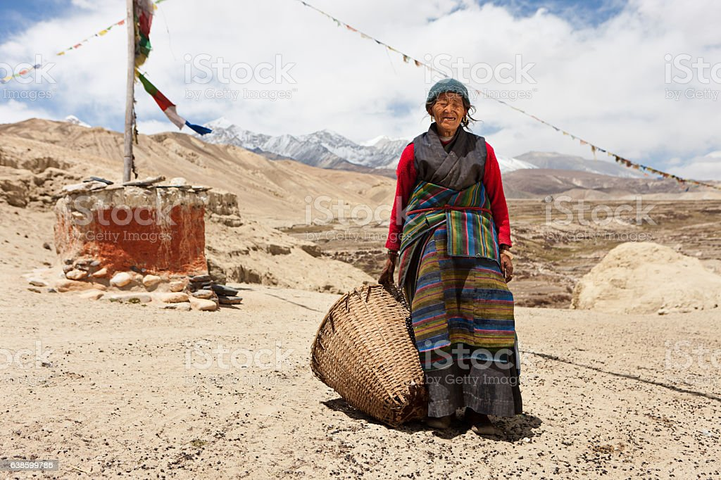 Nepali woman carrying basket in Mustang Region, Nepal stock photo