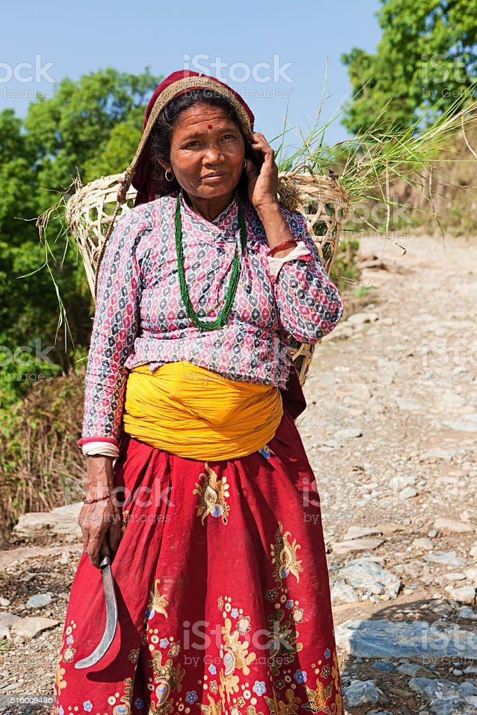 Nepali woman carrying basket in village near Pokhara stock photo