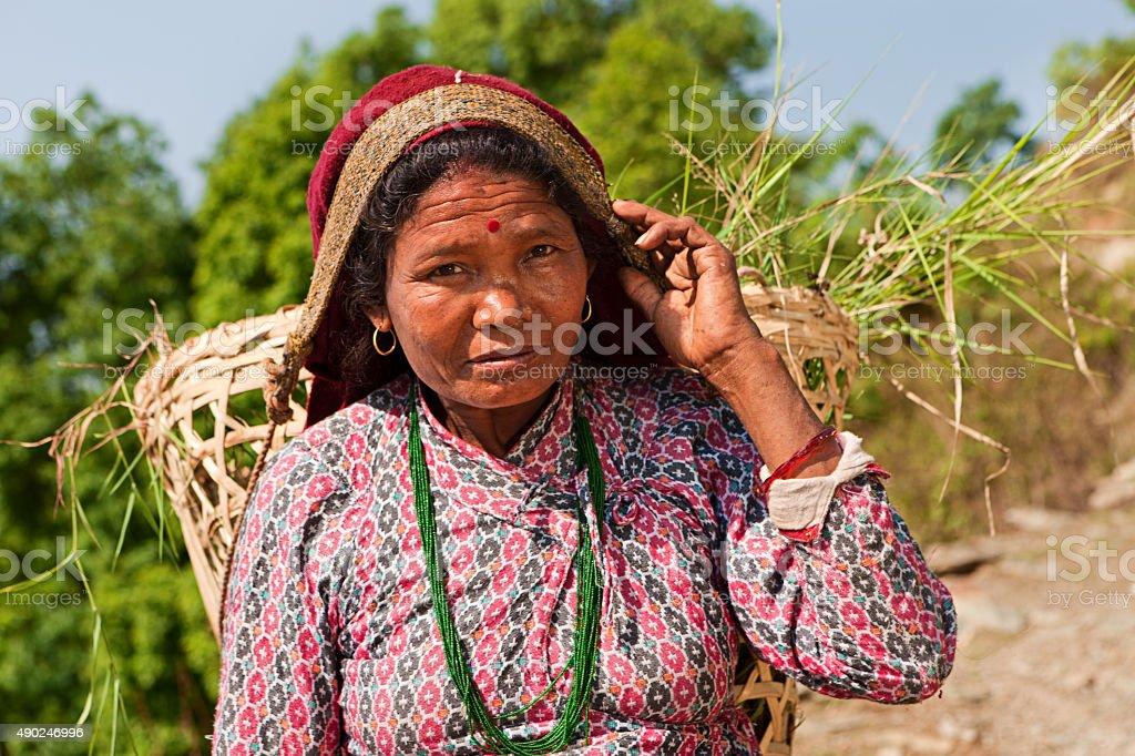 Nepali woman carrying basket near Pokhara stock photo