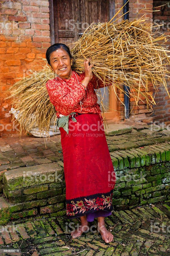 Nepali woman carrying rice straw in Bhaktapur, Nepal stock photo