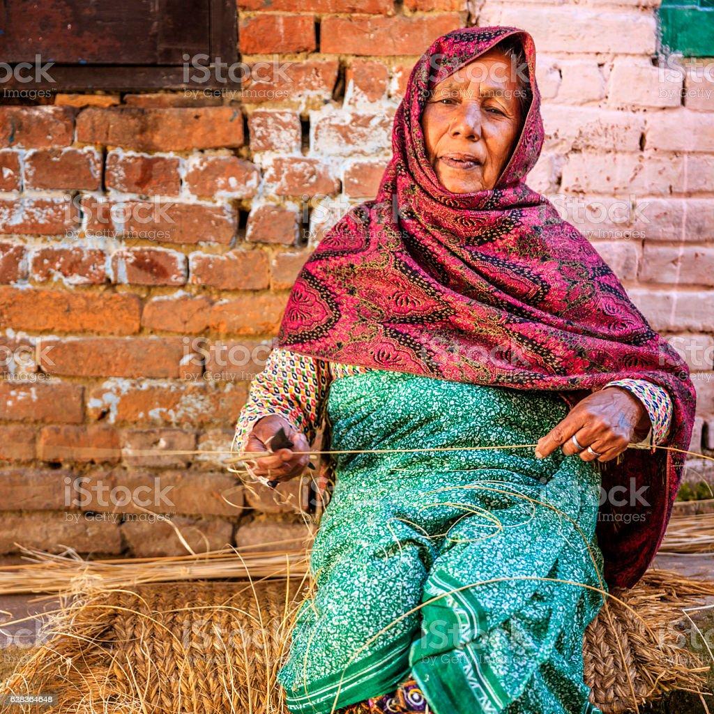 Nepali woman making a broom by hand in Bhaktapur, Nepal stock photo