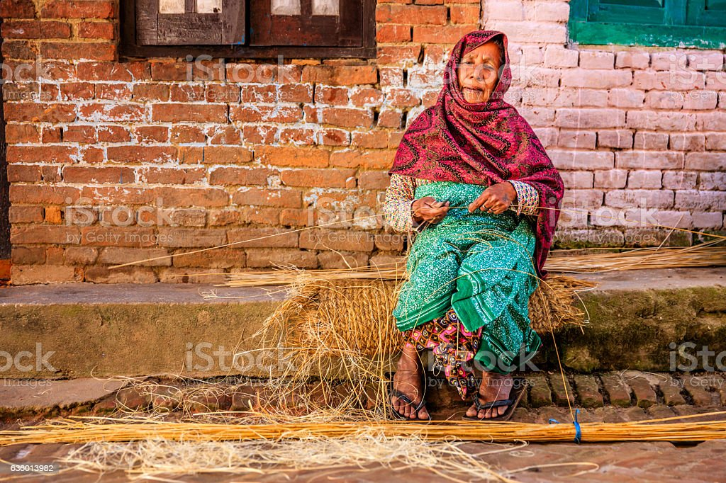 Nepali woman making a broom by hand in Bhaktapur, Nepal stock photo