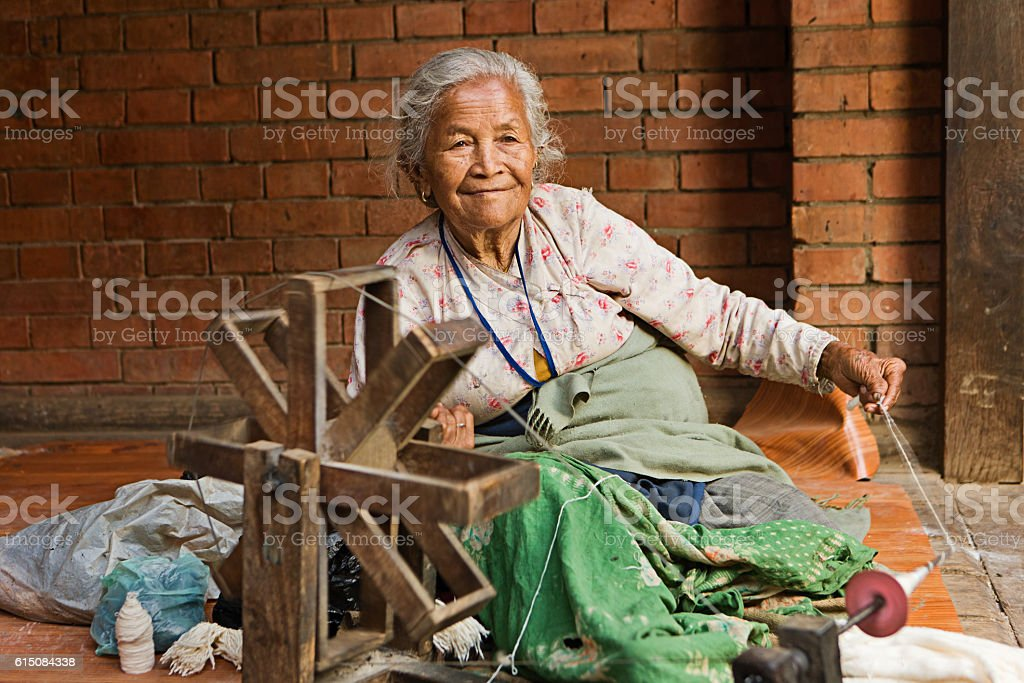 Nepali woman spinning the wool in Bhaktapur stock photo