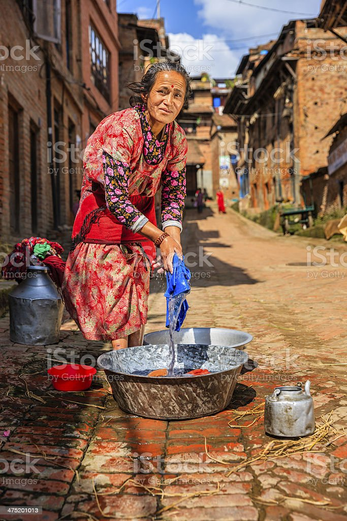 Nepali woman washing clothes on the street in Bhaktapur royalty-free stock photo