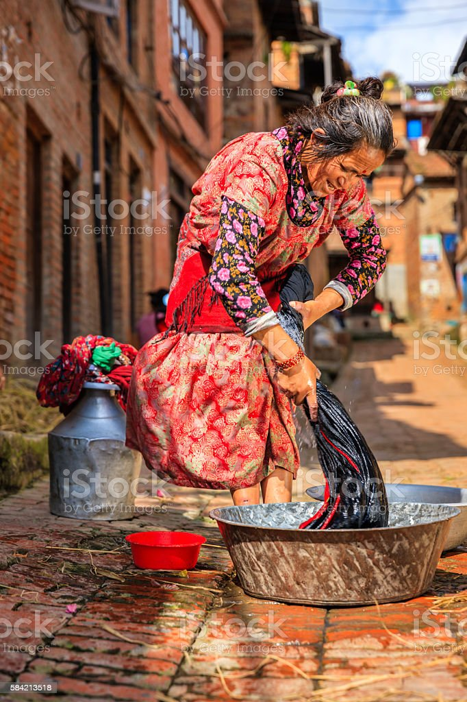 Nepali woman washing clothes on the street in Bhaktapur stock photo