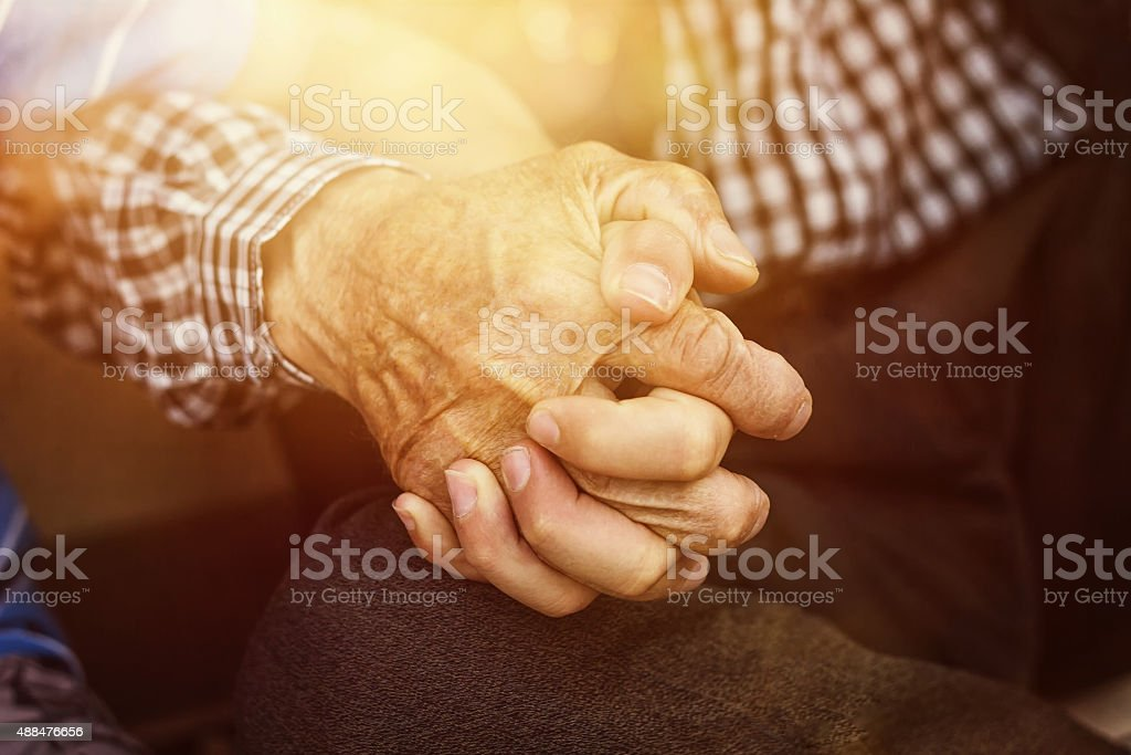 nephew holding strong grandfather's hand stock photo