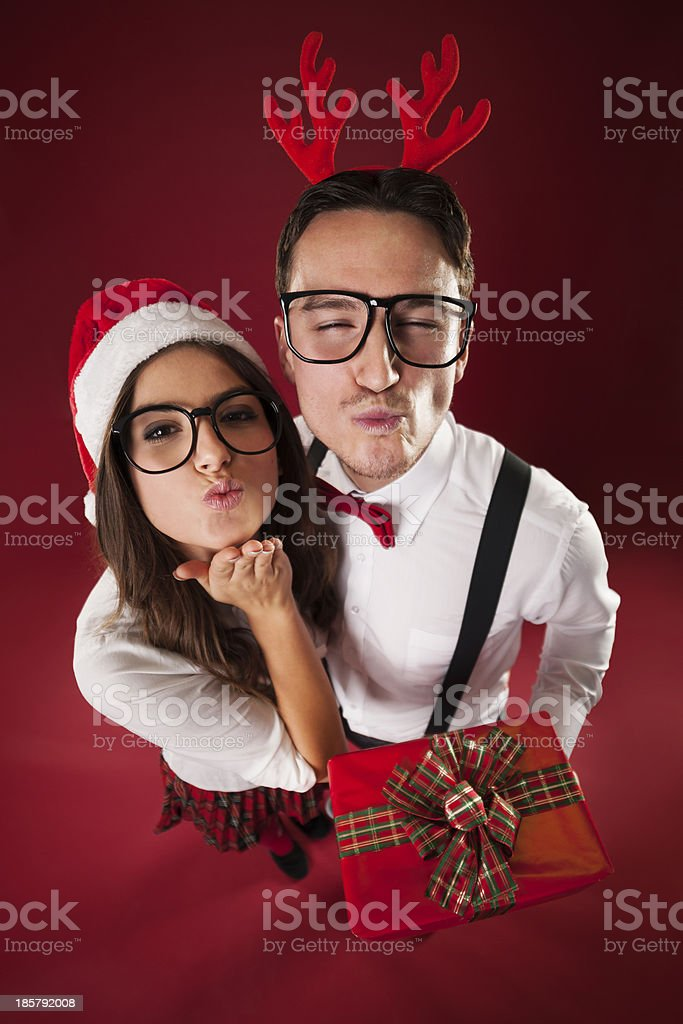 Nerd couple blowing kisses in christmas time stock photo