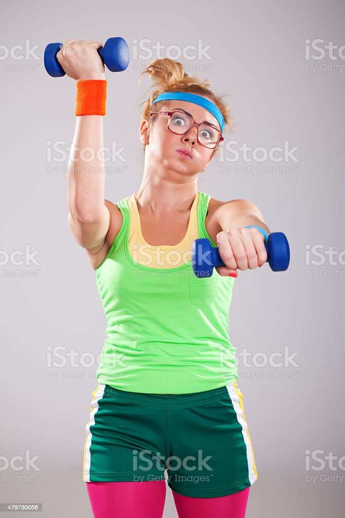 Nerd fitness girl wearing glasses exercising with small weights stock photo
