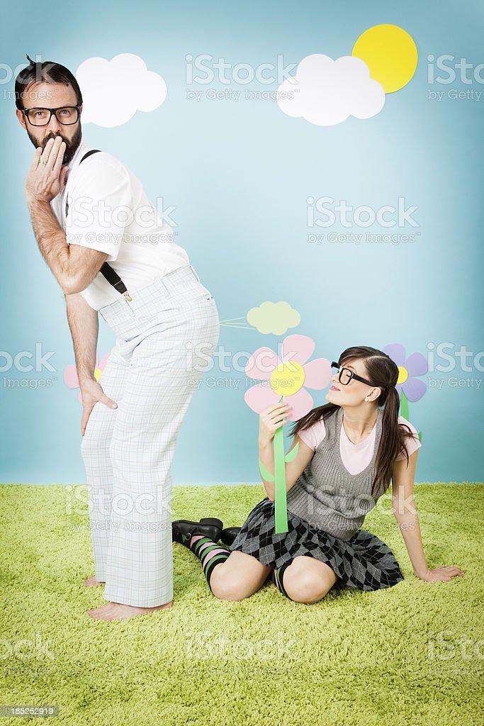Nerd Guy Farting at Nerdy Girl Smelling Flower stock photo