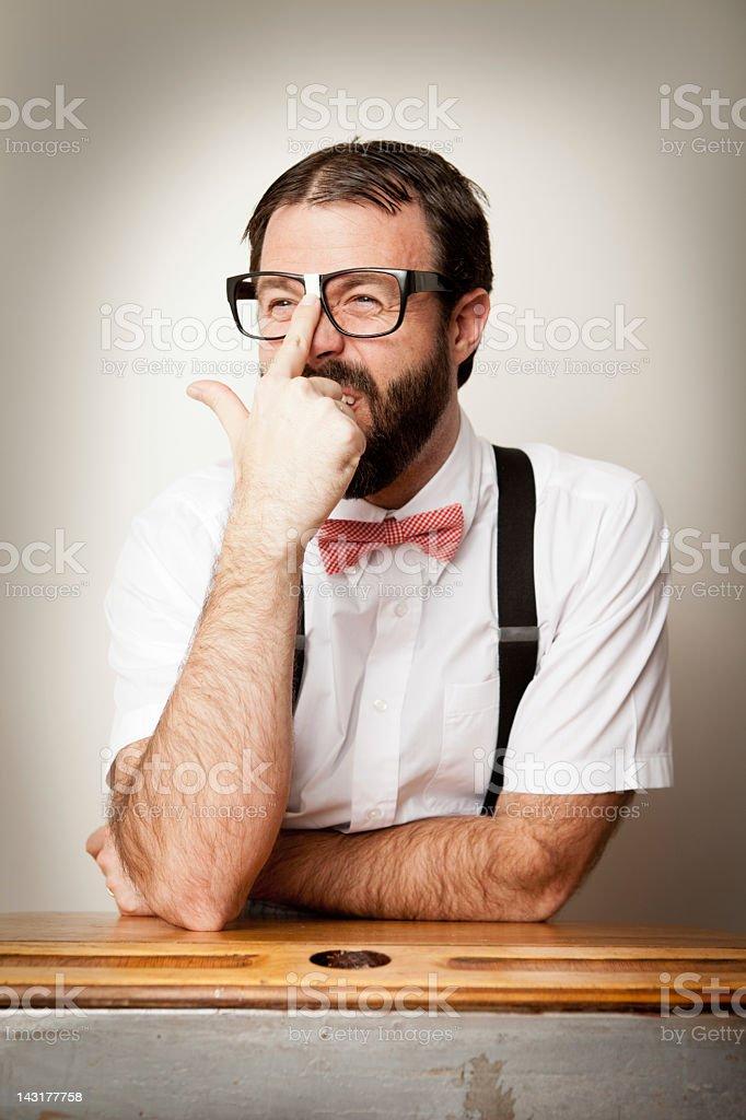 Nerd Guy Sitting at Old School Desk, Pushing Up Eyeglasses royalty-free stock photo
