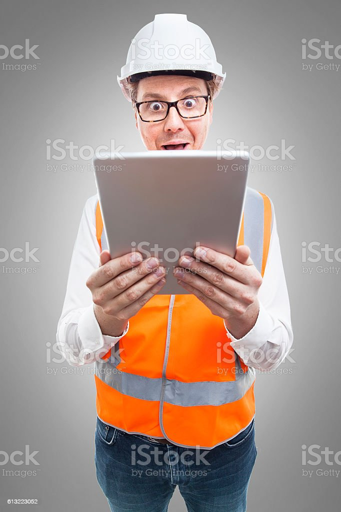 Nerd in safety gear looking at an ipad in astonishment stock photo