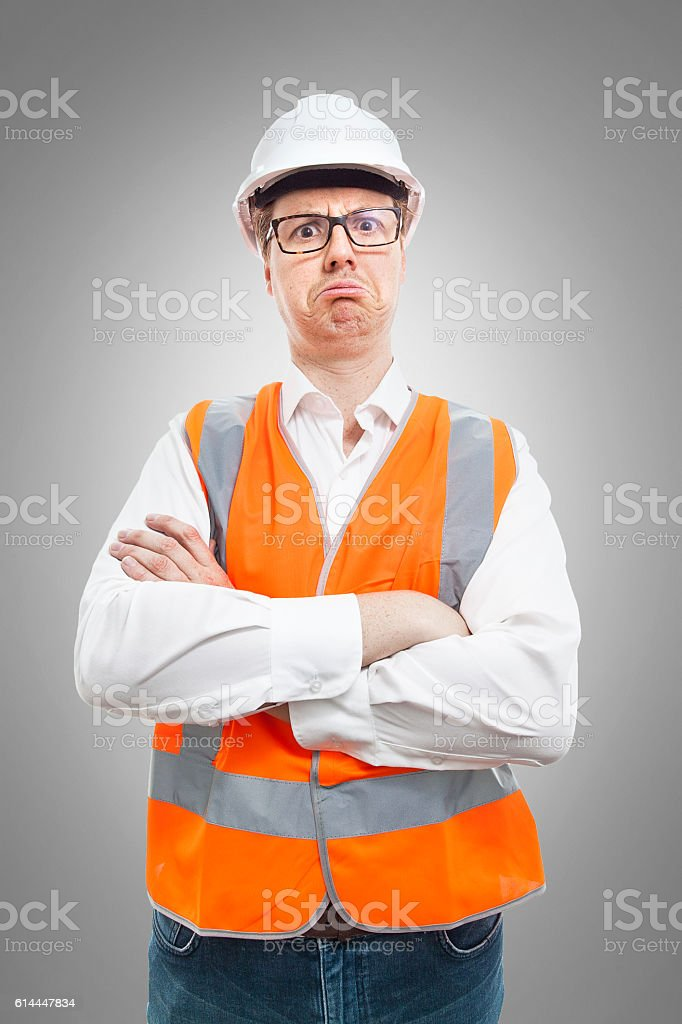 Nerd in safety gear looking worried stock photo