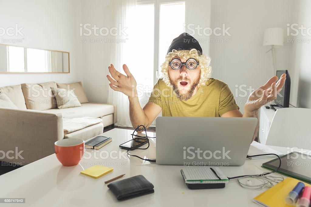 Nerd man working on laptop at home stock photo
