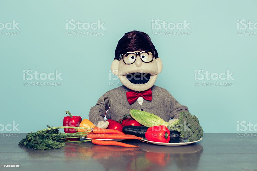 Nerd Puppet Loves Eating Vegetables stock photo