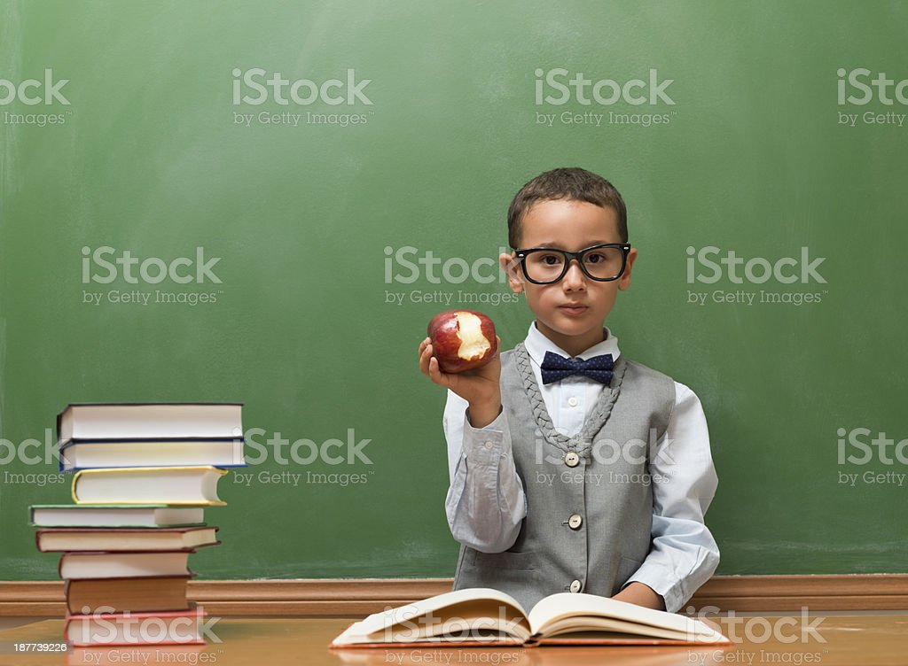 Nerd student eating apple in classroom royalty-free stock photo
