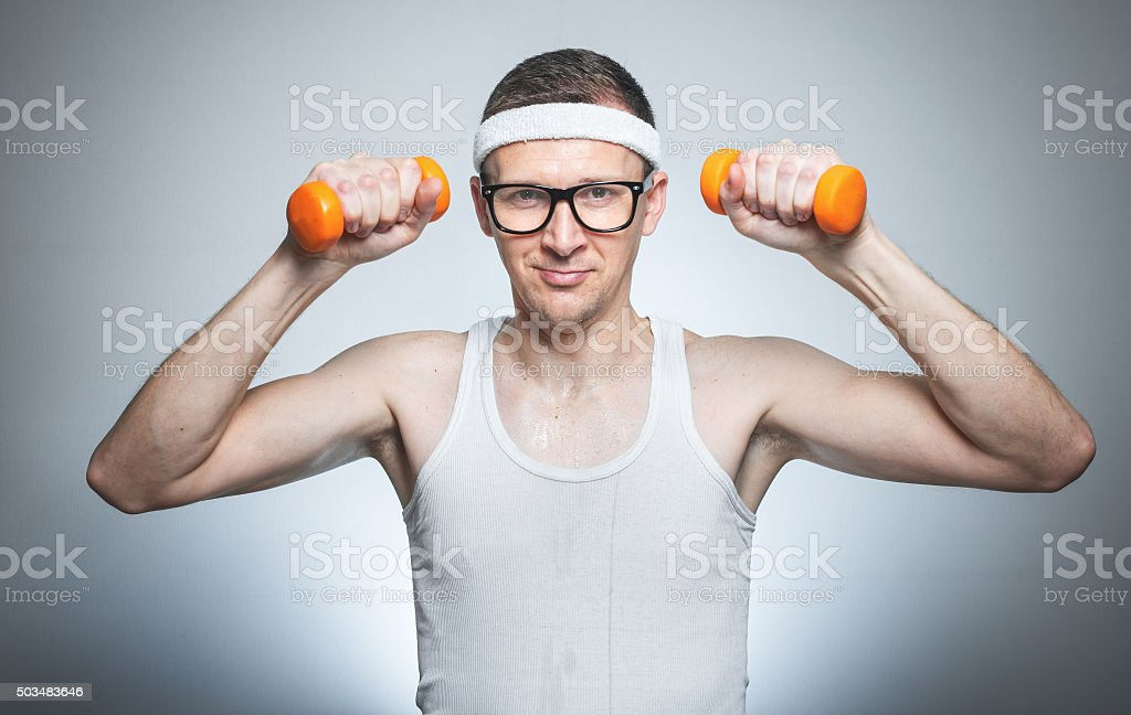Nerd with dumbbells exercising stock photo