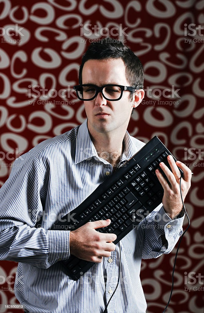 Nerd with eyes narrowed dares you to take his keyboard stock photo