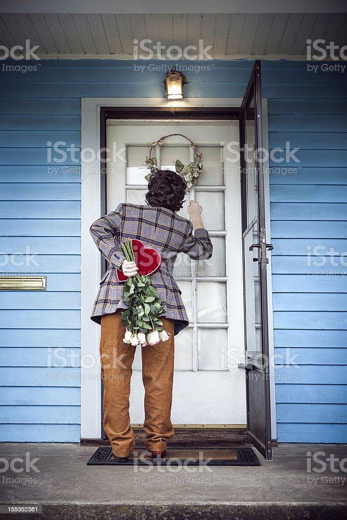 Nerd with Valentine Gift and Flowers Knocks on Door stock photo