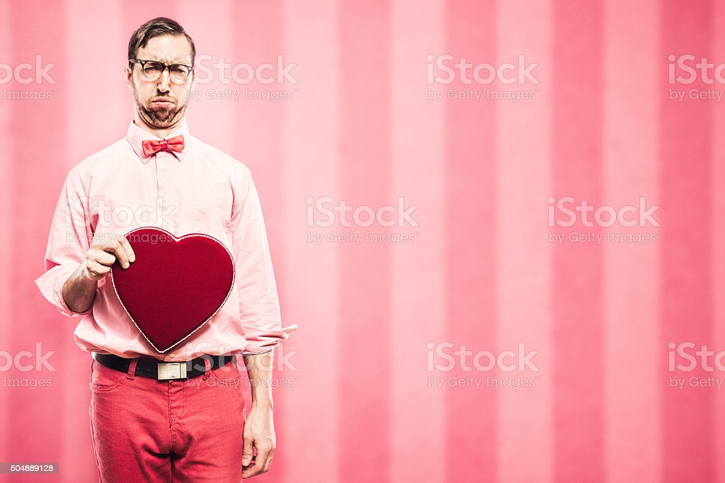 A man in pink and red clothes and a bow tie has a valentine to give...