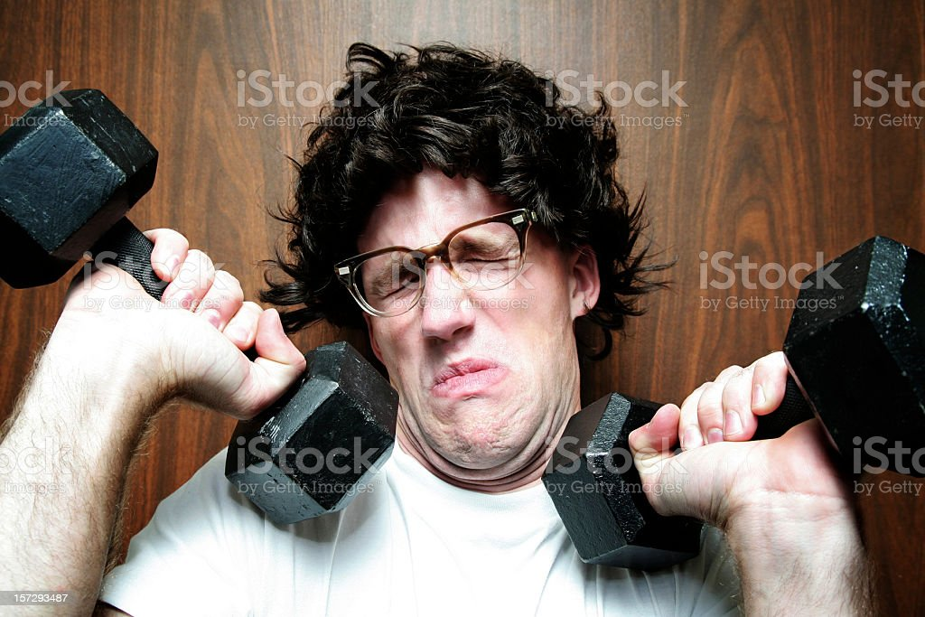 Nerd Young Man Exercising / Weight Lifting royalty-free stock photo