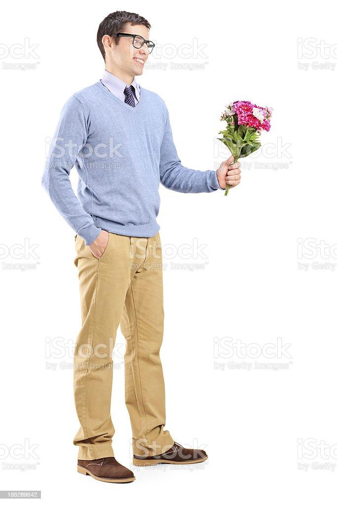 A nerdish man presenting flowers on a white background stock photo