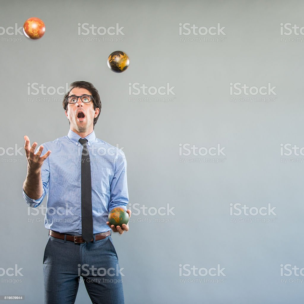 Nerdy Businessman Juggeling Globes stock photo