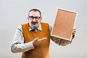 Nerdy businessman with empty cork board