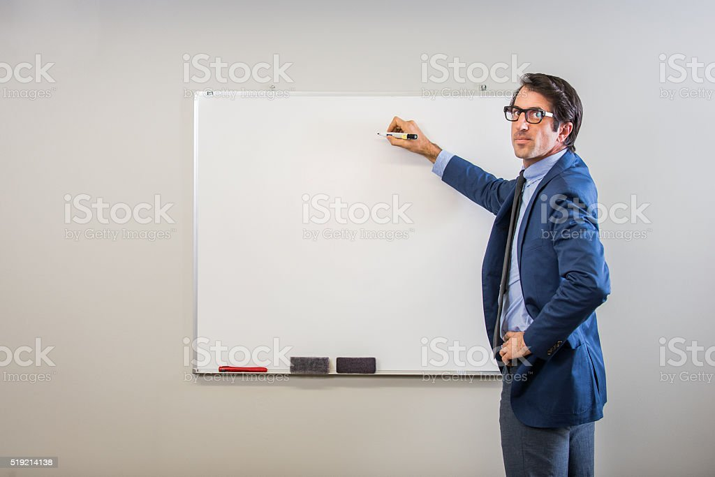 Nerdy businessman writing on a Whiteboard stock photo
