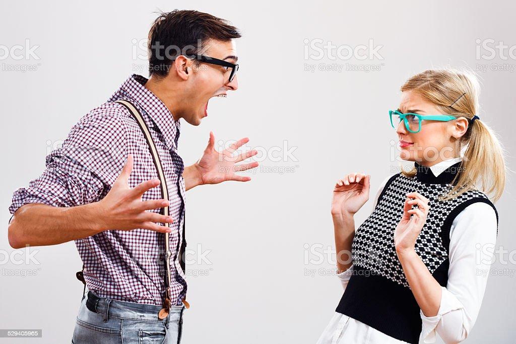 Nerdy couple having conflict stock photo