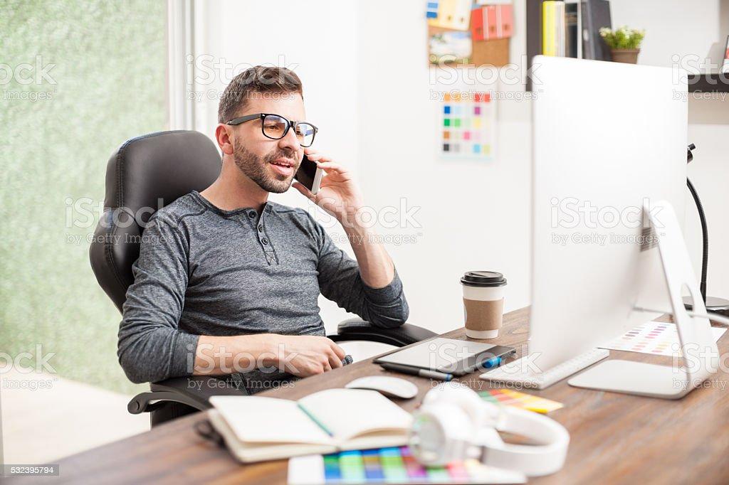 Nerdy designer talking over the phone stock photo