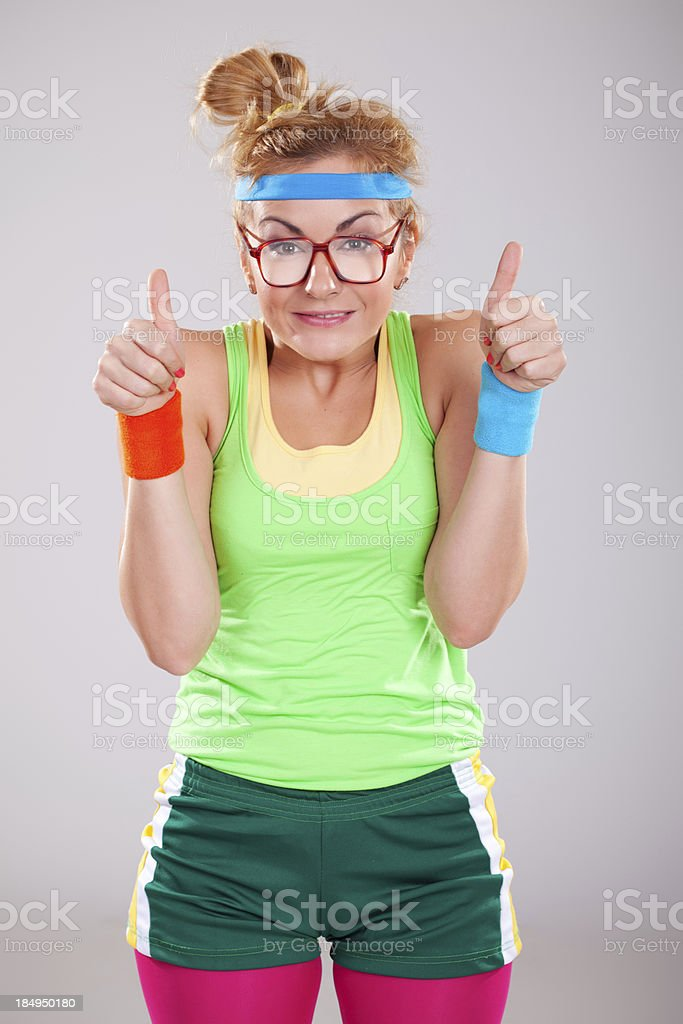 Nerdy fitness girl with glasses holding thumbs up royalty-free stock photo