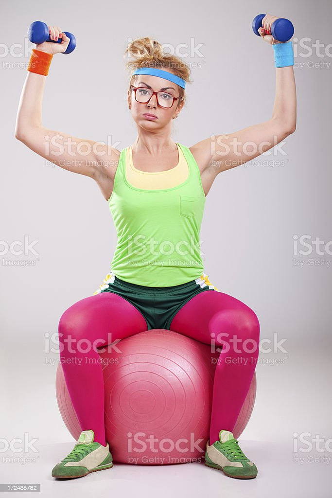 Nerdy girl sitting on pilatess ball and exercising with weights royalty-free stock photo